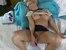 Raunchy Blonde Milf Masturbating On The Bed With A Blue Dildo